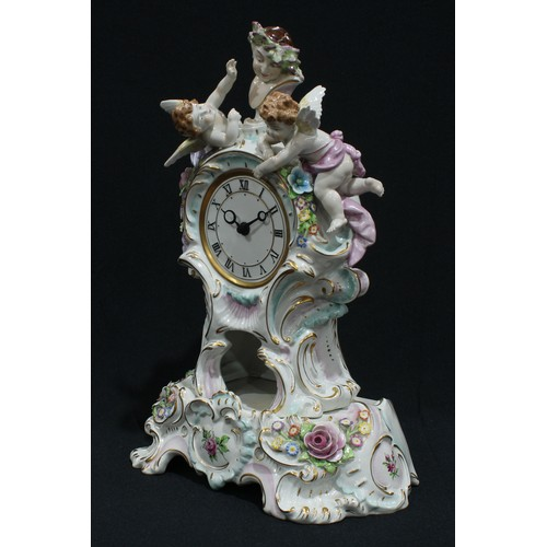 33 - A German porcelain Rococo style mantel clock on stand, surmounted with a Bacchic bust flanked by che...