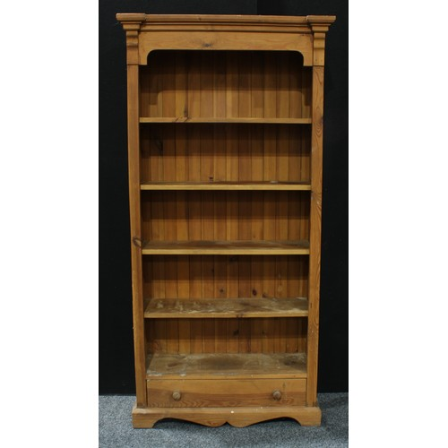 8 - A farmhouse pine open bookcase, outswept cornice above four shelves and a long drawer, 200cm high, 9...