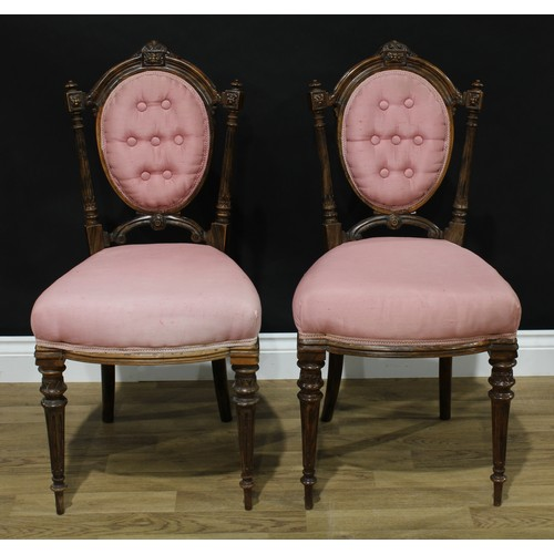 18 - A pair of Victorian imitation rosewood boudoir chairs, each oval back crested by a scrolling acanthu...