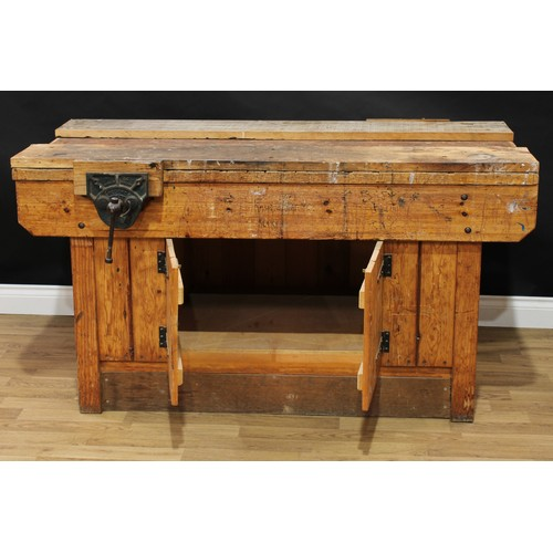6 - A pine workshop/work bench, each long side with a vice, the front with a pair of cupboard doors, 81....