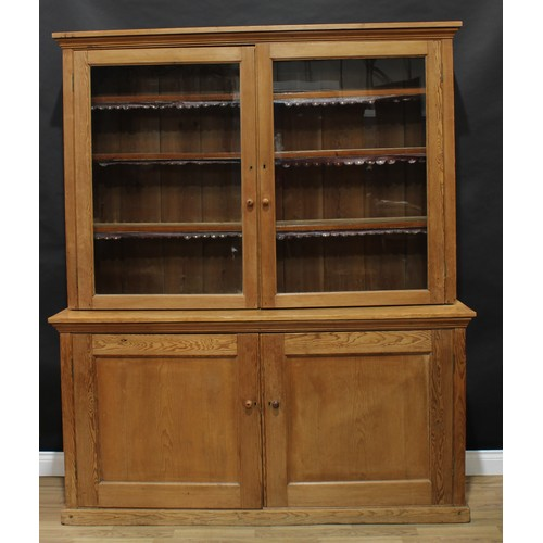 1 - A farmhouse pine housekeeper's dresser or bookcase cabinet, of country house proportions, outswept c...