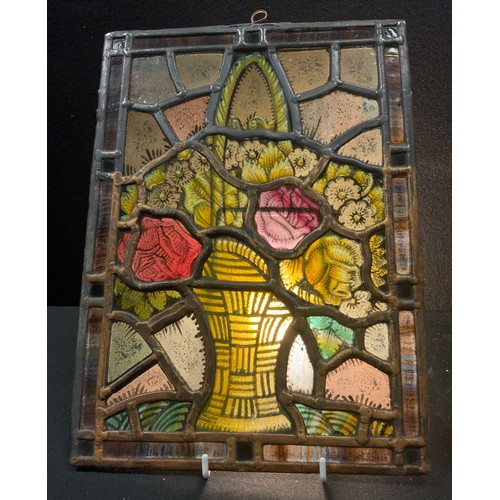 29 - A rectangular painted and stained leaded glass panel, as a basket of Roses and Primroses, 33cm x 24c...