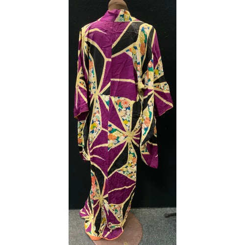 32 - A Japanese Kimono vibrantly decorated with floral and purple panels with star burst framework surrou...