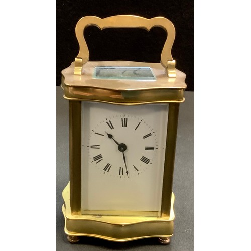 4 - A brass carriage clock, serpentine brass body, Roman numerals. 16cm high.