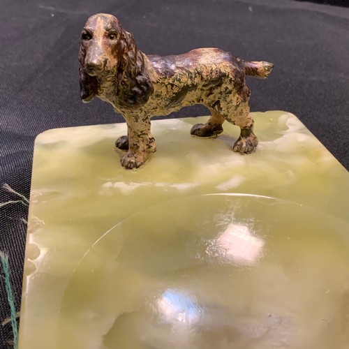 9 - A painted metal figure of a spaniel dog standing, mounted on a green onyx base, 74mm high, 14cm long...