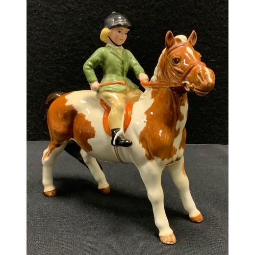 12 - A Beswick model Girl on Pony, 1499, Skewbald, printed marks