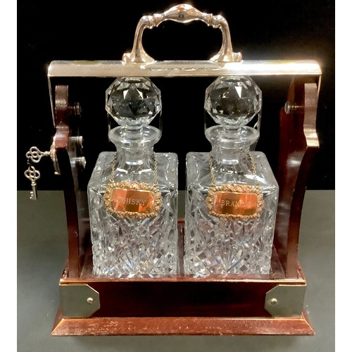 13 - A silver plated two bottle tantalus by Viners, Sheffield, plated whisky and brandy labels....