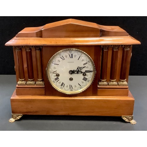 53 - An early 20th century wooden mantel clock, architectural pediment, the face with Roman numerals flan...