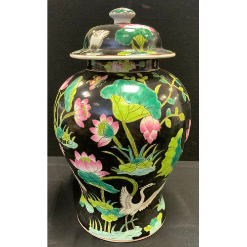 68 - A Chinese famille vert urnular temple jar and cover, printed with birds, lily pads, etc, black groun...