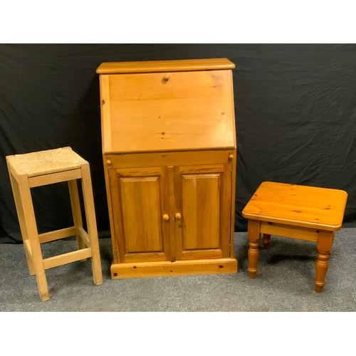 81 - A contemporary pine bureau, fall front enclosing pigeon holes above a pair of cupboard doors, 120cm ...