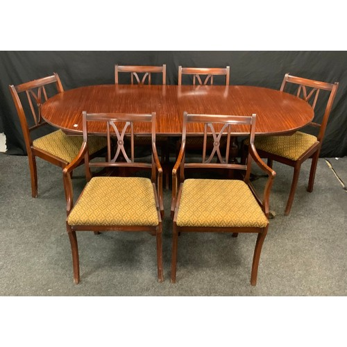 115 - A reproduction twin pedestal extending dining table, oval top, paw feet, brass casters, one addition...