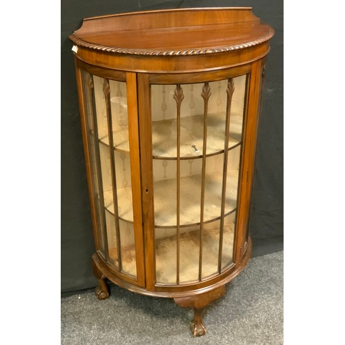 131 - An early-mid 20th century mahogany bow front display cabinet, shaped half gallery above a glazed doo...