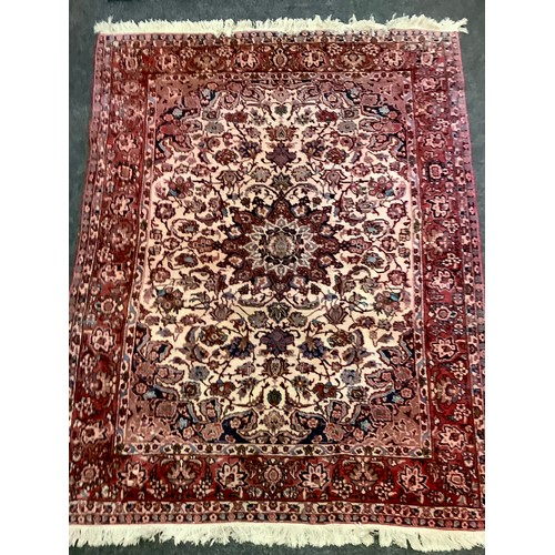 175 - A Middle Eastern handwoven rug decorated with floral patterns in tones of steel blue, indigo and tau...