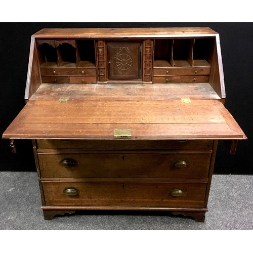 259 - A George III oak bureau, fall front enclosing fitted interior with secret storage, two short cockbea...
