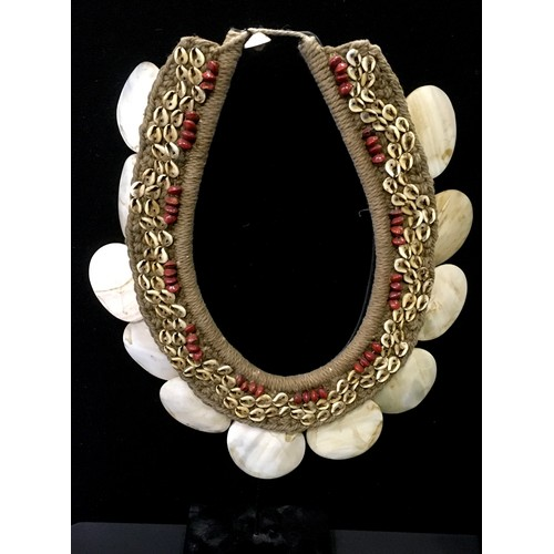 3857 - Tribal Art - a Papua New Guinea neck adornment, composed of graduating cowrie shells and beads on a ...