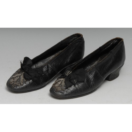 3588 - Costume - a pair of late George III children's black leather court shoes, the silk bows and toes app...