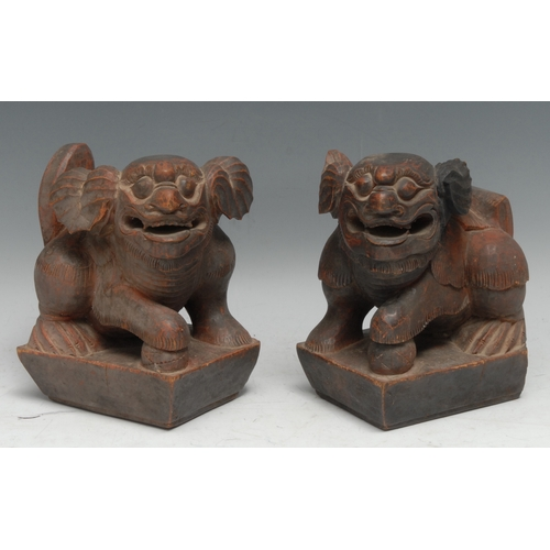 3316 - A pair of Chinese carvings, of temple lions, picked-out in tones of red, 16cm high