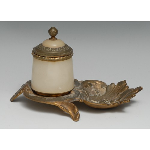 3489 - An early 20th century gilt metal and alabaster inkwell, cast with scrolling acanthus, hinged cover, ...