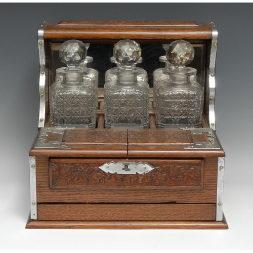 3254 - A late Victorian/Edwardian oak tantalus cabinet, the three hobnail decanters with prismatic stoppers...