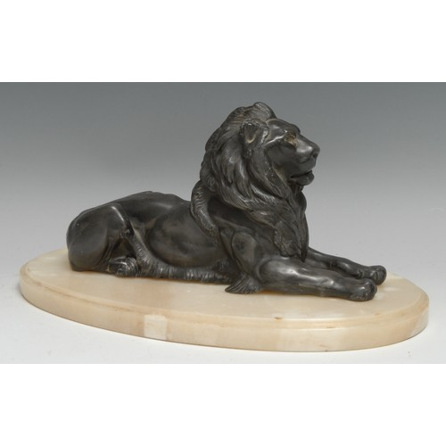 3181 - A French spelter library desk model, of a recumbent lion, oval white onyx base, 31cm wide overall, e...