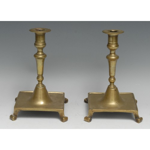 3343 - A pair of Spanish brass table candlesticks, campana sconces with broad rims, scroll feet, 20cm high,...