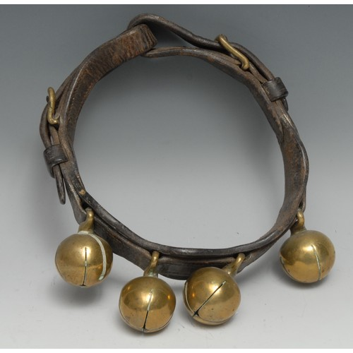 3056 - A 19th century leather animal collar, with four crotal bells, 20cm diam