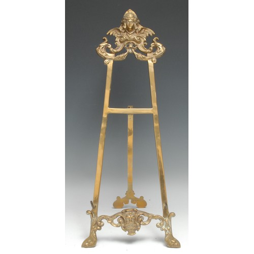 3097 - A Baroque design brass table easel, cast with masks and scrolls, 55cm high