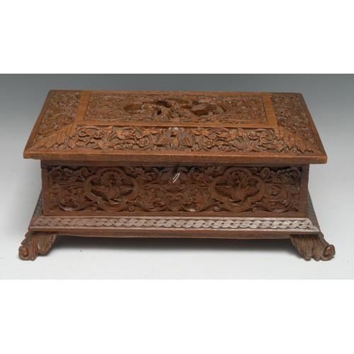3542 - An Indian/Burmese hardwood sarcophagus table box, carved with deities, peacocks and scrolling foliag...