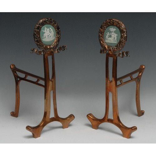 3309 - A pair of Art Nouveau period jasperware mounted copper andirons, each circular cresting set with a p...