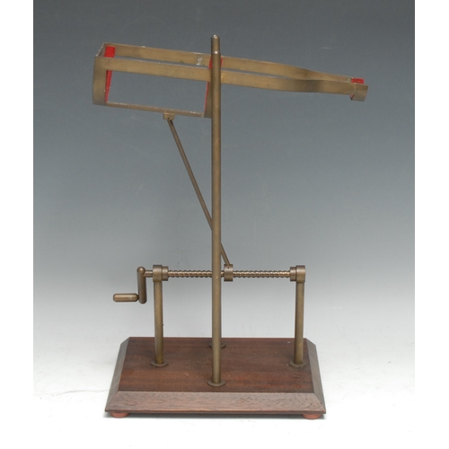 3109 - A brass and mahogany mechanical wine pouring cradle, screw-thread mechanism with cranking handle, re...
