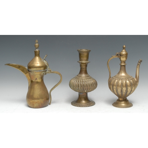 3524 - An Indian brass ewer, of Islamic influence, fluted globular body, mask to spout, domed foot, 28cm hi...