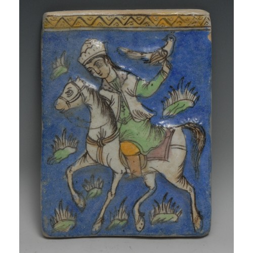 3348 - A Persian rectangular tile, moulded and painted in the typical Qajar taste with a falcolner on horse...