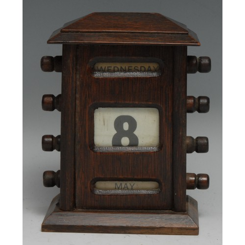 3502 - An early 20th century oak perpetual desk calendar, sarcophagus cresting above glazed apertures for d...