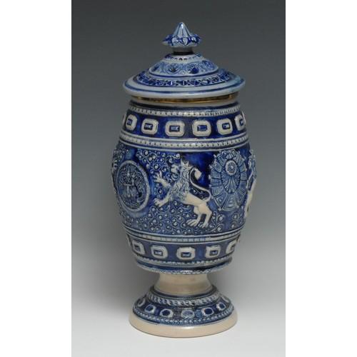 3237 - A large Westerwald salt glazed stoneware pedestal tobacco jar, sprigged with heraldic devices, shell...