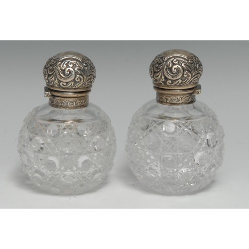 3324 - A pair of Edwardian silver mounted hobnail-cut globular scent bottles, each hinged cover embossed wi...