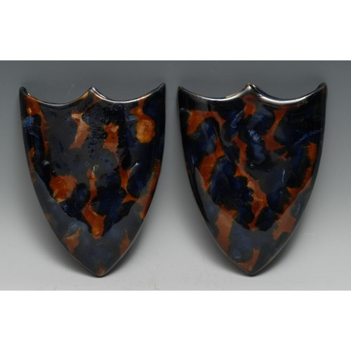 3322 - A pair of Denby stoneware shield-shaped wall pockets, glazed in mottled tones of blue and brown, 20c...