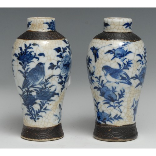 3315 - A pair of Chinese baluster vases, painted with flowers, birds and winged insects in underglaze blue ...