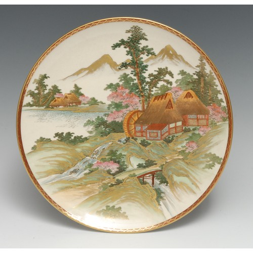 3215 - A Japanese Satsuma circular plate, typically in polychrome and gilt with a watermill at the foot of ...