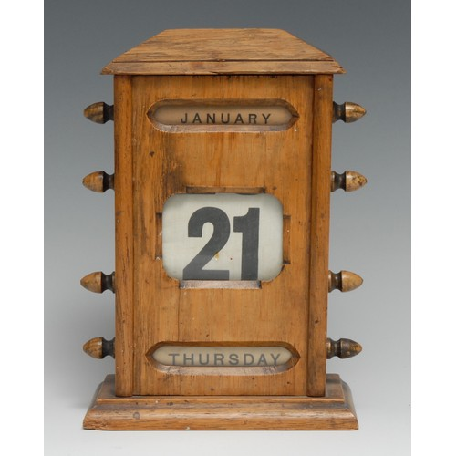 3503 - An early 20th century oak perpetual desk calendar, sarcophagus cresting above glazed apertures for m...