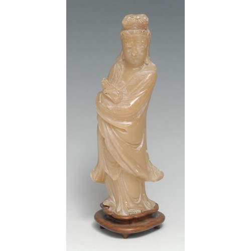 3157 - A Chinese soapstone carving, of Guanyin, she stands, holding a scroll, hardwood stand, 22cm high ove...