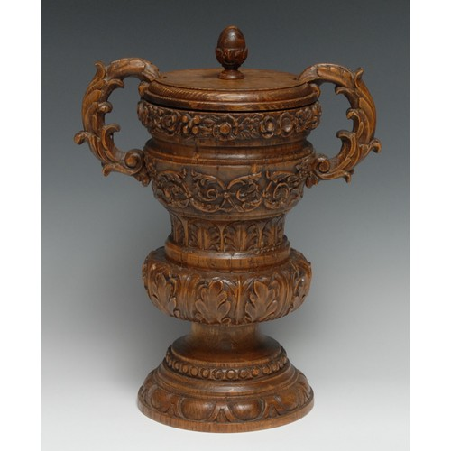 3224 - A large 19th century oak tobacco jar and cover, of country house proportions, boldly carved througho...