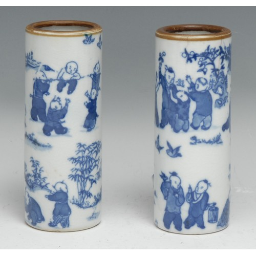 3317 - A pair of Chinese cylindrical vases or brush pots, decorated in tones of underglaze blue with The Hu...