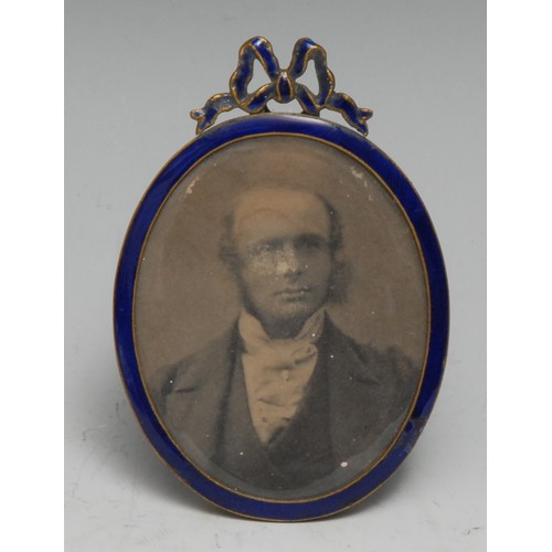 3477 - An early 20th century blue enamel oval easel portrait miniature or photograph frame, ribbon cresting...