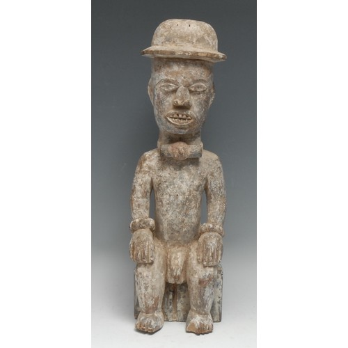 3875 - Tribal Art - an Igbo figure, carved as a seated man, white pigment, 40cm high, Nigeria