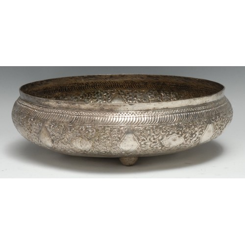 3541 - An Indian silver coloured metal circular bowl, chased with dense scrolling foliage and lozenge shape...