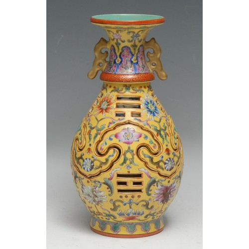 3150 - A Chinese ovoid reticulated puzzle vase, painted in polychrome enamels with flowers on a yellow grou...
