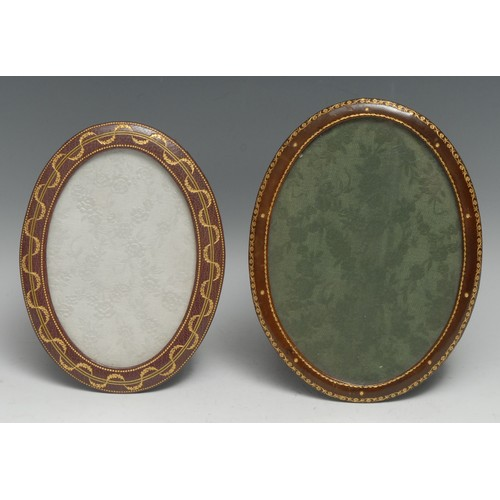 3506 - An early 20th century tooled and gilt leather oval easel photograph frame, retailed by Walter Jones,...