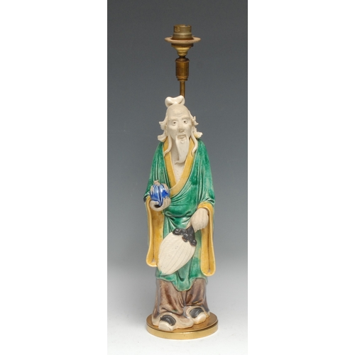 3133 - A Chinese figure, of an elder holding a peach, glazed in mottled tones of green, yellow, and blue, 3...