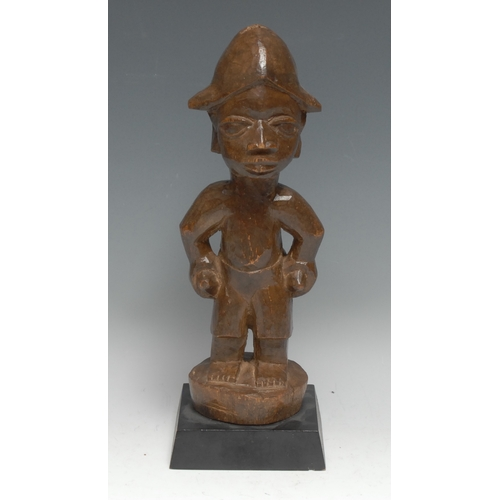 3863 - Tribal Art - a Yoruba figure, he stands, with each hand full, 33cm high, Nigeria, ebonised connoisse...