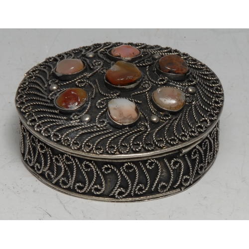 3273 - A Middle Eastern silver coloured metal circular box, applied with wirework scrolls and applied with ...